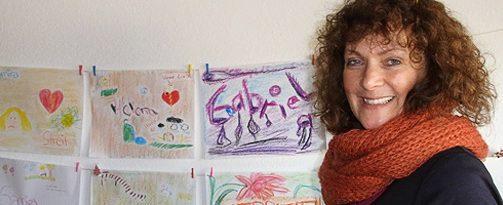 Frau Apel vor einer Bilderwand